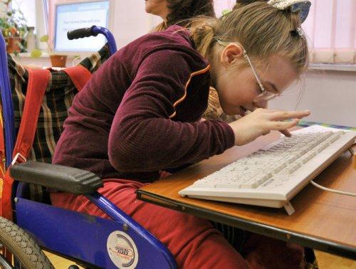 Ребенок в инвалидной коляске за компьютером