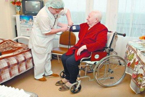 Медработник измеряет давление у пациента