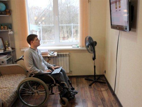 Мужчина в инвалидной коляске в комнате смотрит телевизор
