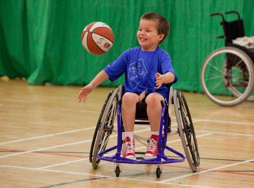 Ребенок с мячом в инвалидной коляске