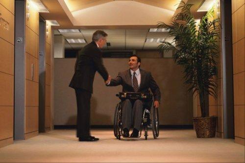 Инвалид-колясочник здоровается за руку с мужчиной