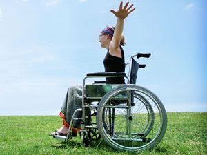 Женщина в инвалидной коляске в поле